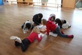 Kinder liegen am Boden und erledigen Aufgaben