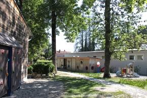Gartenanlage mit hohen Bäumen und Materialraum