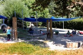 Sandlandschaft mit blauem Segeldach und Holzbrücke